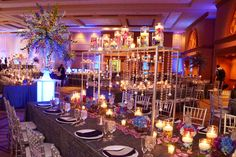 Long table centerpiece with hanging crystals and cylinders filled with orchids and floating candles. WHOA BABY!