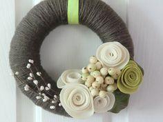 Corona recubierta de lana con combinacion de flores de fieltro y bacche artificiales.