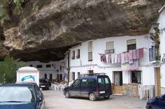The photographs are genuine and depict a real town. However, the town, called Setenil de las Bodegas, is actually located in Spain, not Greece.