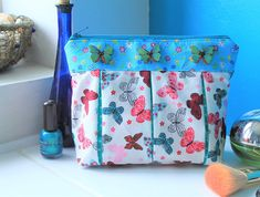 Cosmetic bag, toiletry bag or wash bag.  This make up pouch is dainty and cute, with the added bonus of being very practical too. The cotton butterfly fabric is pleated with a co-ordinating polka dot cotton underneath. It is fully lined in a pale pink with daisies. I have interfaced