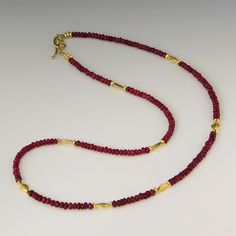 An 18k yellow gold, long ruby bead necklace with gold kite spacers and wavy toggle clasp. 17 Inches Long by Barbara Heinrich