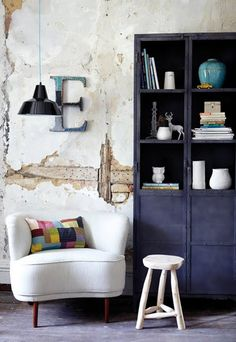 love the colorful pillow and the dark bookcase. personally i would replaster the wall, the look is charming, yet...