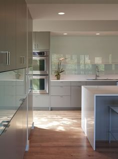 Don't like this splash back, Sleek #kitchen with caesarstone counters and glass backsplash.