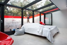 Advantages of Using Transparent Glass in Your Home : Contemporary Bedroom With Glass Wall And Ceiling With Small Balcony And Red Chair
