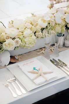 Starfish punctuate clean white place settings for an elegant, beachy feel.