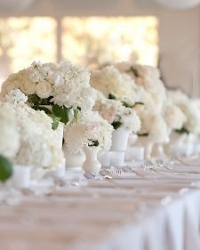 White flower centerpieces with white vases & vessels, hydrangea & greenery. Photo by Front Room.