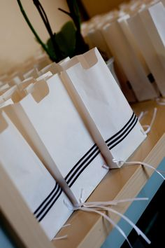 Regular white paper bags with strings for tzitzis and black and white ribbon! Just cut a 'neck' out of the top! Voila! Tzitzis favor bags!