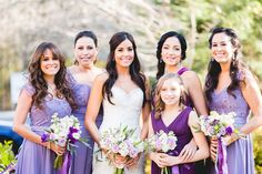 The bride carries a pastel bouquet of white and lavender roses; the bridesmaids and flower girls have varying shades of purple and lilac dresses and beribboned bouquets.    Venue: 103 West in Atlanta