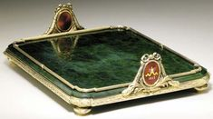 A Silver-Gilt guilloché enamel nephrite tray  marked Fabergé and th mark of Henrik Wigström, St. Petersburg, 1908-1917 - Rectangular with stylized rounded corners, the nephrite plaque set with a ribbon-tied reeded border and with a ribbon-tied laurel-leaf rim surmounted by two oval cartouches enclosing a vari-colored enamel Imperial crown emanating from a red guilloché enamel sunburst ground and with the date 1613 and 1913 - palm leaves and wreaths surmounted by a ribbon, on  ball feet…
