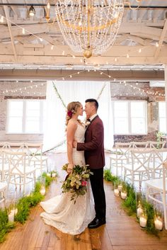 http://Bride%20and%20groom%20under%20chandelier%20at%20modern%20winter%20wedding%20at%20The%20Stockroom%20at%20230