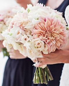 The bridal bouquet - cream hydrangeas, ivory roses, blush pink dahlias, blush pink spray roses, and white sweet peas wrapped in gold ribbon with the stems showing.
