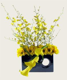 yellow calla lilies, oncidium orchids, daisies centerpiece