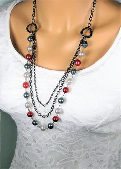 Long Beaded Necklace with Multi Strands of Black Chain, with large Red, Green, and Silver Pearl Beads. Handmade by Ralston Originals. This beaded necklace is made with large glass pearl beads in red, silver, and green/grey beads. The colors in this necklace would make a great