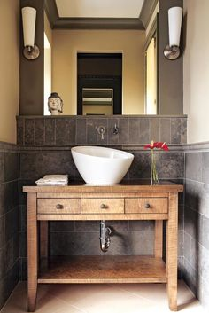 The powder room features wainscoting made of Portuguese limestone, a handsome backdrop for the custom birds-eye maple cabinet. Cabinetry, stained birds-eye maple, by Phil Plunket Custom Cabinetry. Wall faucet, Falling Water by Kohler. Sink, Crucible by Kohler. Lights, Marina from DWR. Wainscoting and floor, Walker Zanger.