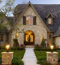 Light your home for evening curb appeal...love the stone and the front doors.