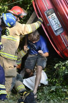 The driver of a Mercury Mystique crawls out of his vehicle after being extricated through the back window by Chattanooga Fire Department firefighters August 21 when his vehicle ran off the road and flipped into some trees at the intersection of Riverside Dr. and Appling St.