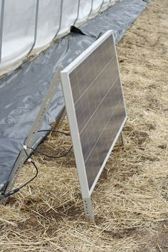 A small solar panel runs the fan that helps insulate the hoophouse.
