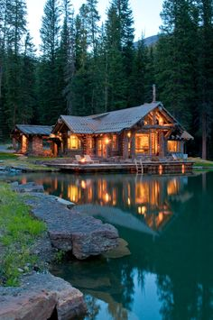 Log cabin is on dock over lake; Headaters Camp, Big Sky, Montana