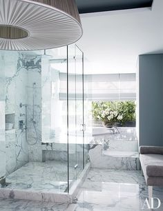 A marble-lined bath in the Colombian home of handbag designer Nancy Gonzalez has a spacious shower appointed with Dornbracht fittings   archdigest.com