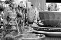 Original y cálido almuerzo en el jardín de la casa. Armado de mesa con flores en frascos de vidrio y combinación de vajilla de distintos estilos y colores. Imagen en blanco y negro.