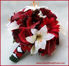 Red, burgundy, white, and black bouquet featuring deep red calla lilies, red roses, red gerbera daisies, white lilies, and more. Triple layer stem wrap of white, red, and black.
