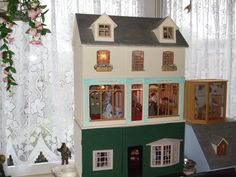 one of my new dolls house shop and on the bottom is a room box with two rooms,  the room box is a drapery shop and the dolls house is a ladies shop with a two story family home above.