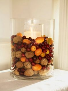 Heaped with walnuts, cranberries, and kumquats, a cylinder vase displays festive flavors. Place a tall (8- to 12-inch) pillar candle and holder inside the vase; surround with fruits and nuts.