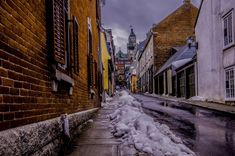 #alley #architecture #buildings #city #house #light #melting #narrow #outdoors #pavement #road #slippery #snow #street #town #travel #wall #wet #window #winter