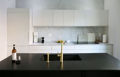 A marble slab draws the eye upward in the kitchen. Brass Kitchen Faucet, Kitchen Fixtures, Bathroom Faucets, Gold Faucet, Bathrooms, Wood Cabinet Doors, Wood Cabinets, Brooklyn Brownstone, Minimal Kitchen