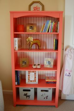 Coral Painted Bookcase with Gold Lines Wallpaper on the Back - what a lovely statement piece!