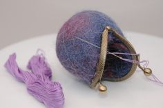 Sewing a tiny clasp to a wet felted coin purse with contrasting embroidery thread
