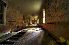 """For over 20 years, abandoned Hellingly has been dying, fading, and peeling, but there is a lovely quality that makes you shudder about the ruination. Some explorers have reported hearing unexplained noises up and down the many corridors. Of course, old buildings make noises. The hallway above is one that was in """"better"""" condition than many others."""