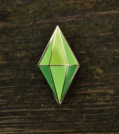 This 1.25 gold plated hard enamel pin features the Plumbob character icon from EAs The Sims series. All Pin15 lapel pins have 2 posts on the back and butterfly clasps so you never have to worry about them spinning or coming loose.