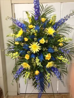 Fresh funeral spray using blue delphiniums, yellow Fuji mums, yellow snapdragons, yellow roses, white wax flowers accented with Royal blue ribbons throughout spray. June 2016.