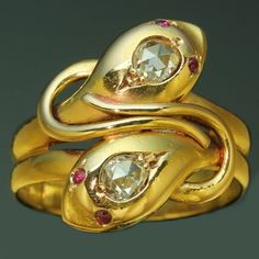 Double snake serpent Victorian ring with rose cut diamonds and rubies  Victorian gold double snake ring. The design of the ring features two intertwined snakes, rendered in gold with a rose cut diamond on top of their heads and two rubies for eyes. This kind of snake rings were very popular in the Victorian period due to the fact that Queen Victoria was given such a ring by Albert as engagement ring.C 1890