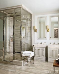 The master bath of this Southampton, New York, house decorated by Steven Gambrel, the shower walls and floor are travertine, and the sconces are by Jacques Adnet. Tour the rest of the home.   - ELLEDecor.com