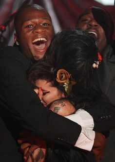 British singer Amy Winehouse is hugged by band member Zalon at The Riverside Studios for the 50th Grammy Awards ceremony on February 10, 2008 in London, England.