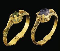TWO GOLD BRACELETS   SELJUK IRAN, 12TH/13TH CENTURY   Each of hinged bevelled form, with central pronounced domed elements with inset stones, flanking these stones a crouching feline, its tail scrolling down beneath it, the shaft of each bracelet with cartouches of black niello benedictory naskh inscription alternated with pronounced quatrefoil medallions