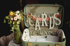 Take one old suitcase, add cardboard letters (CARDS), add bits and pieces of pretties that appeal to you. Place on a table where you add 3-4 8x10 framed candid photos.  Add in a few wine glasses turned upside down with a battery operated candle in the bottom and a mardi gras spray on top and VOILA!  You have a centralized place for people to place gifts and cards!