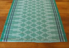 This Scandinavian style table runner would make a wonderful compliment to your home. The runner features two different shades of green; very pale green and leaf green with two bands of purple running the length of the runner. Hand woven in the Ripsmatta or Rep weave method, it features distinctive small loops of weft that are created on the edges of the runner. In this weave the weft isn't seen in the main body of the weaving but it is used to create a ridge like texture. Long triangles in…