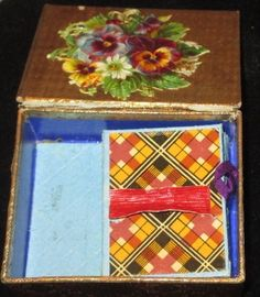 19thc English needle case covered with paisley paper and a scrap decorated mirrored lid. Gold metallic paper lid, plaid paper needle paper holders inside   (interior)