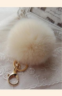 Pom Pom Keychain in cream. Faux fur ball with a 14K gold plated key ring and clasp is a beautiful addition to your bag, keys or belt. Have fun!