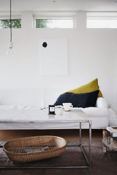 White sofa. Open, clean design coffee table. Simple industrial light bulb. Graphic wall art. Details with color and woven basket to create warmth and personality.