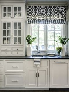 Dark floors and countertops, and white cabinets. outside mount patterned roman shade above sink