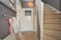 Hal in Voorburg met kapstok/plankje bij verwarming en geschilderde lambrisering langs de trap