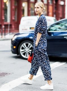 Pernille Teisbaek wears a floral jumpsuit, white sneakers, a classic gold watch, and a red top-handle bag