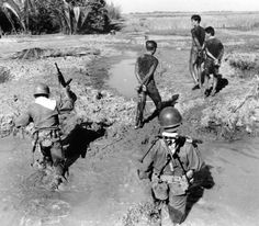 Vietnamese soldiers and communist prisoners cross a creek in Bac-Lieu village on December 25 1962.