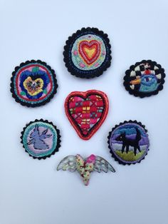 Embroidered pins, plus one heart with wings made from tin. Created by: Mary Stanley, USA Funky Jewelry, Jewelry Art, Jewellery, Embroidery Fashion, Hand Embroidery, Heart With Wings, Textile Jewelry, Textiles, Felt Ornaments