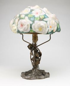 A Pairpoint 'Puffy' reverse painted art glass and patinated metal ''Rose Bouquet'' lamp, First quarter 20th century, the closed-top, shaped domed ''Rose Bouquet'' shade with partially rubbed patent mark to shoulder rim, above a single-socket fitment with straight smooth stem entwined with roses over a molded floral base.