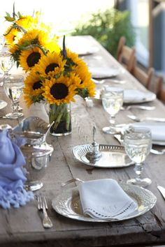 I like the consistency of the silver flatware, cream plates and napkins and crystal stemware paired with the jolt of sunflower yellow.